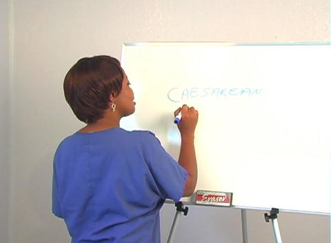 "Beautiful Nurse Writes ""Caesarean Section"" on a White Board Footage"