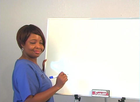 "Beautiful Nurse Writes ""Cataracts"" on a White Board Stock Video Footage"