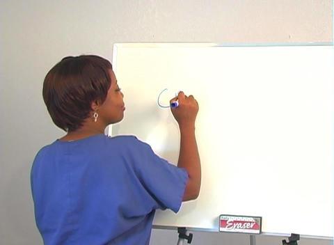"Beautiful Nurse Writes ""Cataracts"" on a White Board Stock Video Footage"