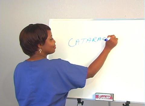"Beautiful Nurse Writes ""Cataracts"" on a White Board Footage"