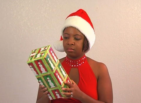 Beautiful Woman Shakes a Christmas Gift (1) Stock Video Footage
