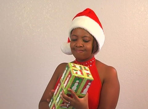 Beautiful Woman Shakes a Christmas Gift (1) Footage
