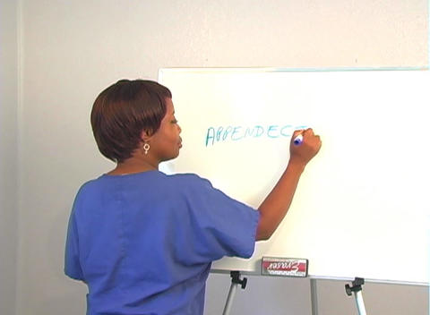 "Beautiful Nurse Writes ""Appendectomy"" on a White Board Footage"