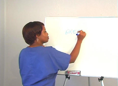 "Beautiful Nurse Writes ""Breast Biopsy"" on a White Board Stock Video Footage"
