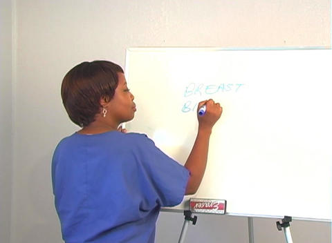 "Beautiful Nurse Writes ""Breast Biopsy"" on a White Board Stock Video Footage"