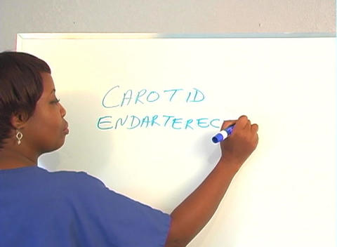 "Beautiful Nurse Writes ""Carotid Endarterectomy"" on a White Board (close-up) Footage"