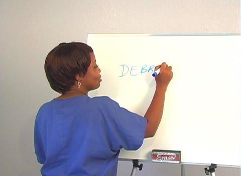 "Beautiful Nurse Writes ""Debridement"" on a White Board Stock Video Footage"