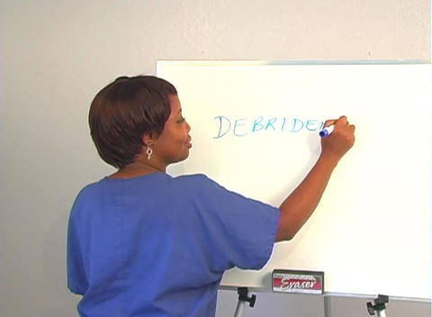 "Beautiful Nurse Writes ""Debridement"" on a White Board Footage"