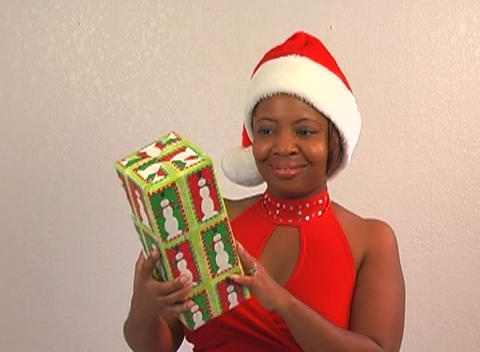 Beautiful Woman Shakes a Christmas Gift (2) Footage