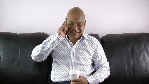 African man drinking while talking on phone Stock Video Footage