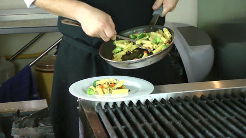 Chef serving rigatoni in the kitchen Stock Video Footage
