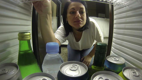 woman looks in the fridge very hungry and doesn't  Footage