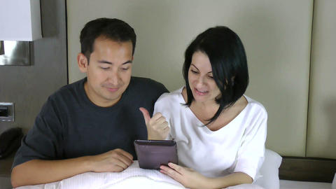 happy couple sitting on bed and looking at the tab Stock Video Footage