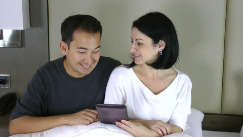 Happy Couple Sitting On Bed And Looking At The Tab stock footage