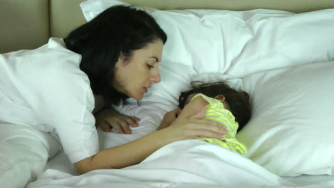 Mother wakes up her daughter in the bedroom Footage