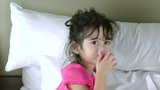 Little girl in bed taking medicine Footage