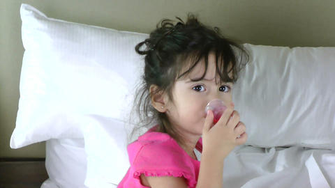 Little girl in bed taking medicine Stock Video Footage