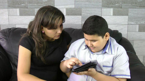 Elementary school boy studying on tablet with moth Stock Video Footage