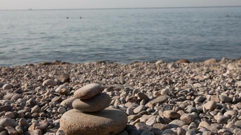 Man building stone pyramid on the sea beach Stock Video Footage