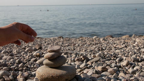 Man building stone pyramid on the sea beach Stock Video Footage