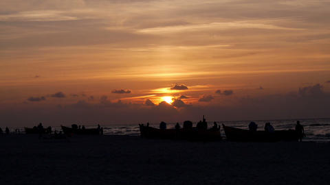 People and boats on the beach - silhouettes Stock Video Footage