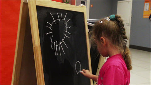 little girl drawing sun with chalk on blackboard Stock Video Footage