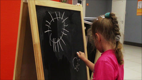Little Girl Drawing Sun With Chalk On Blackboard stock footage