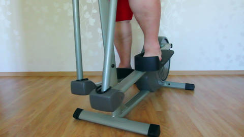 overweight woman legs exercising on trainer ellips Footage