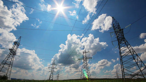tall electric masts against sun and cloudy sky - t Stock Video Footage