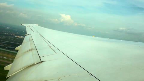 WINDOW VIEW OF WING PLANE OVER GROUND Stock Video Footage