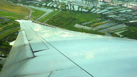 WINDOW VIEW OF WING PLANE OVER GROUND stock footage