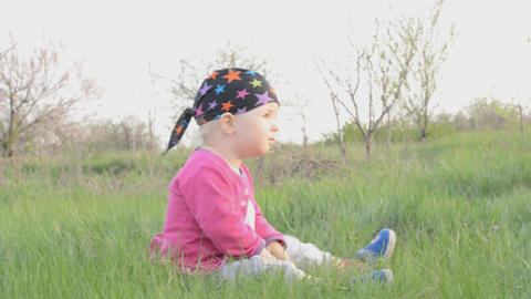 Baby sits on a grass, dolly shot Footage