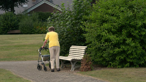 pensioner sit down painfully on park bench 11085 Stock Video Footage