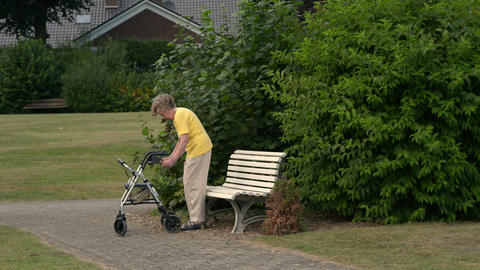 Pensioner Sit Down Painfully On Park Bench 11085 stock footage