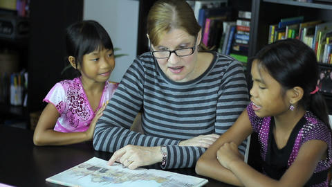 Homeschool Mom Reads To Asian Daughters Stock Video Footage
