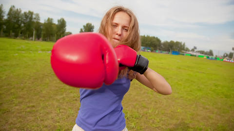 The girl in boxing gloves in a meadow Stock Video Footage