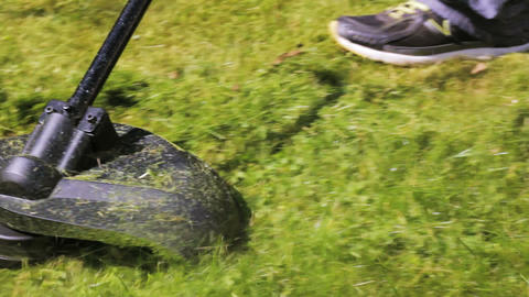 Cutting grass with lawn mower. Close Up Footage