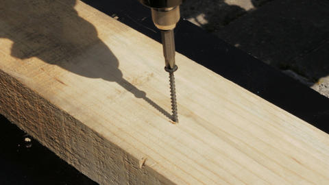 Carpenter driving screw into wooden desk Footage