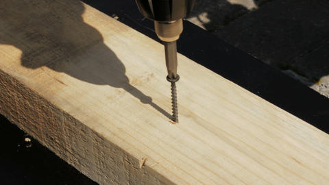 Carpenter driving screw into wooden desk Stock Video Footage