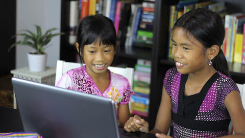 Two Asian Sisters Laugh Using A Laptop Computer Stock Video Footage