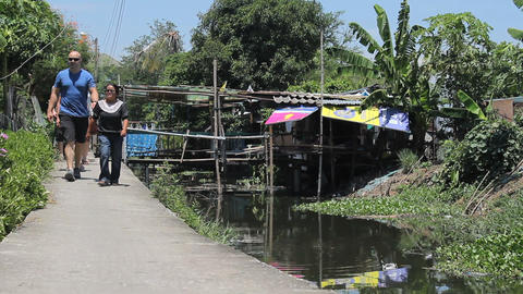 Young Adults Visiting Slum Homes Along The Canal Stock Video Footage