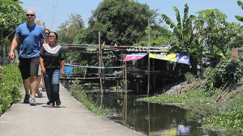 Young Adults Visiting Slum Homes Along The Canal stock footage
