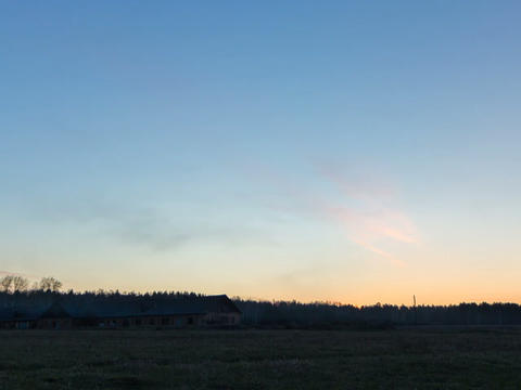 Sunset over the field with a barn. Stars appear. T Footage