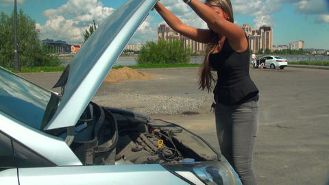 Blonde opens the hood of a car Footage