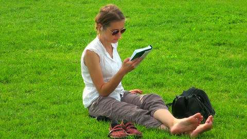 Girl with a book on the grass Stock Video Footage