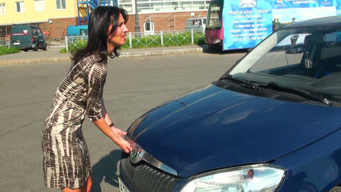 Brunette in the hood of the car Stock Video Footage