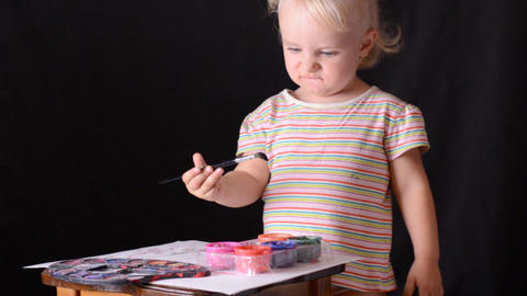 Cute little baby painter on black background Footage