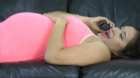 Pregnant woman laying down in the sofa talking on Stock Video Footage