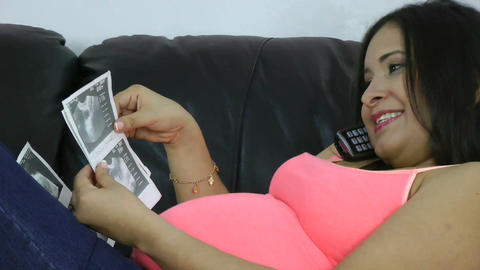 Pregnant in the phone with her baby's ultrasound s Stock Video Footage