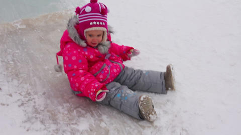 little girl on winter ice slide Footage